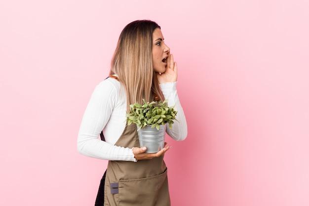 叫び、開いた口の近くの手のひらを保持している植物を保持している若い庭師女性。