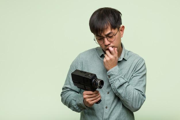 Молодой китайский человек, держащий старинные камеры расслабился, думая о чем-то, глядя на копией пространства