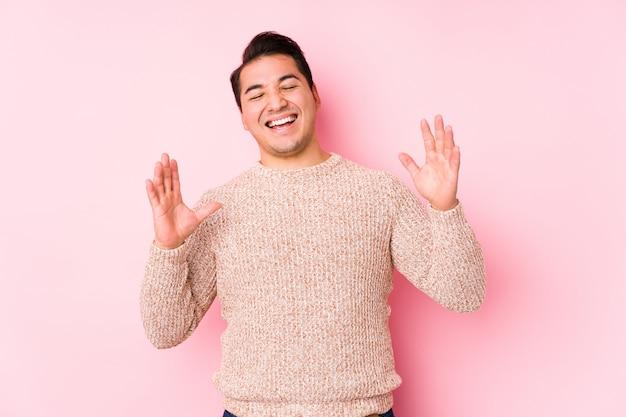 ピンクの壁でポーズをとって若い曲線の男は、うれしそうな笑いをたくさん分離しました。幸福の概念。