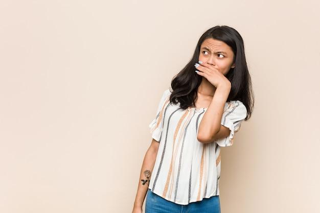 若いかわいい中国のティーンエイジャー手で口を覆っているコピースペースを探して思慮深いピンクの壁にコートを着ている若いブロンドの女性。