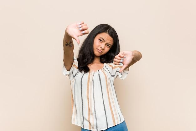 若いかわいい中国のティーンエイジャーダウン親指を示すと嫌悪感を表現するピンクの壁にコートを着ている若いブロンドの女性。
