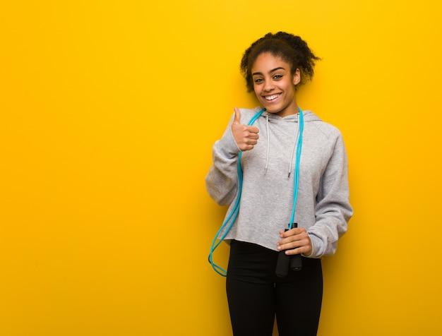 Молодой фитнес черная женщина улыбается и поднимать палец вверх. держа скакалку.