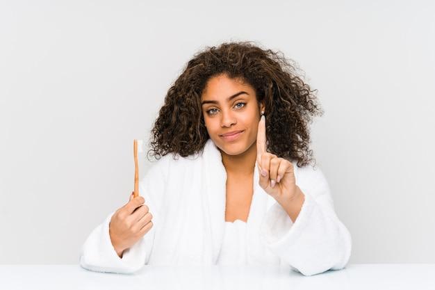 指でナンバーワンを示す歯ブラシを保持している若いアフリカ系アメリカ人女性。