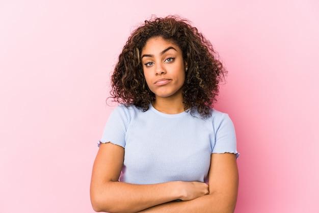 皮肉な表現に不満のあるピンクの壁に若いアフリカ系アメリカ人女性。