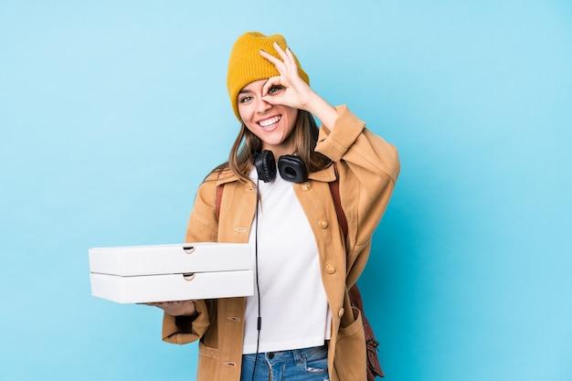 Молодая кавказская женщина держа пиццы изолировала возбужденный держать одобренный жест на глазе.