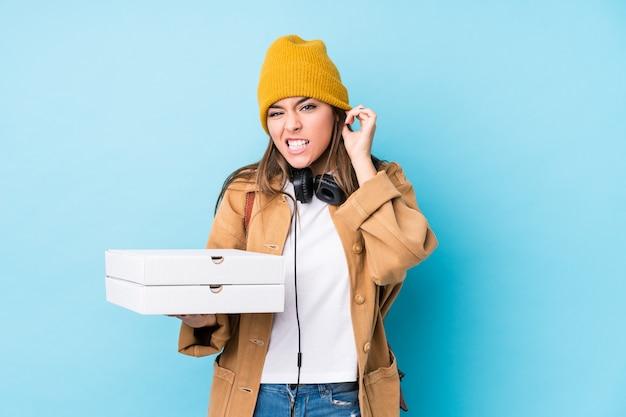 Молодая кавказская женщина держа пиццы изолировала покрывать уши руками.