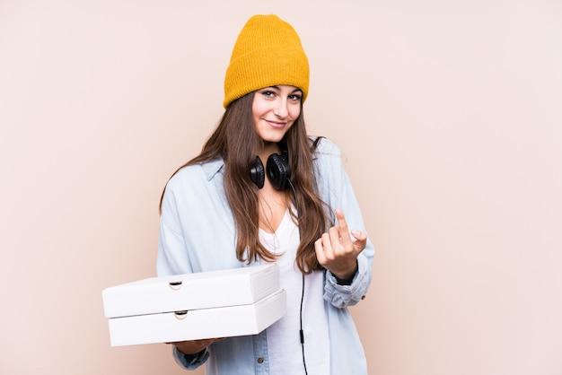 ピザを保持している若い白人女性は、あなたに指を指して分離されて、まるで招待が近づくように。