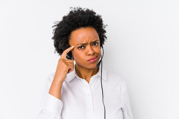 Молодая афро-американская женщина телемаркетера изолировала указывать висок с пальцем, думая, сфокусированным на задаче.