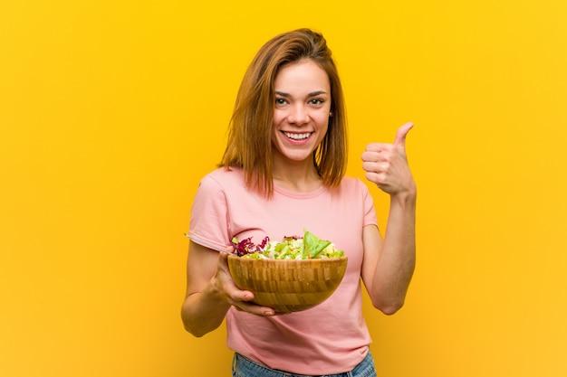 Молодая здоровая женщина, держащая салат, улыбаясь и поднимая большой палец вверх