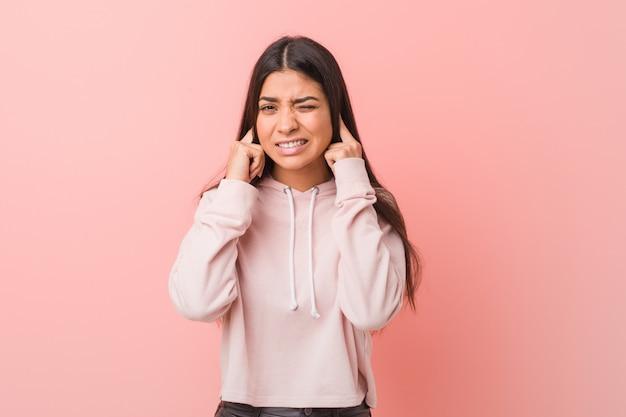 手で耳を覆っているカジュアルなスポーツの外観を着ている若いかなりアラブの女性。