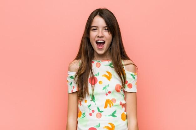 非常に怒って攻撃的な赤い壁に夏服を着ている少女。