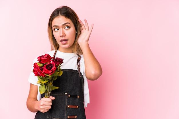バラを保持している若い白人女性は、ゴシップを聞いてしようと分離しました。