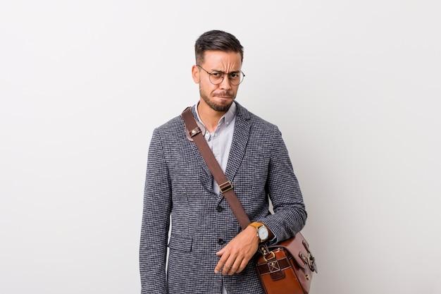混乱している白い壁に対して若いビジネスフィリピン人男性は、疑わしく、自信がありません。