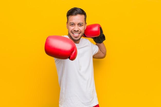 赤い手袋を身に着けている若い南アジアボクサー男。