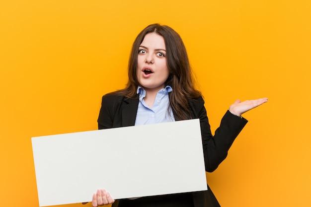 Молодые плюс размер соблазнительная женщина с пустым белым плакатом на руке