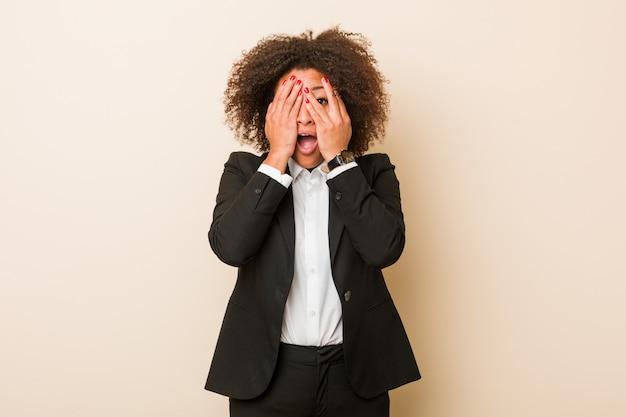 Молодой бизнес афро-американских женщина мигать сквозь пальцы испуганные и нервные.
