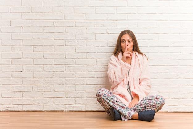 Молодая женщина в пижаме держит в секрете или просит молчать