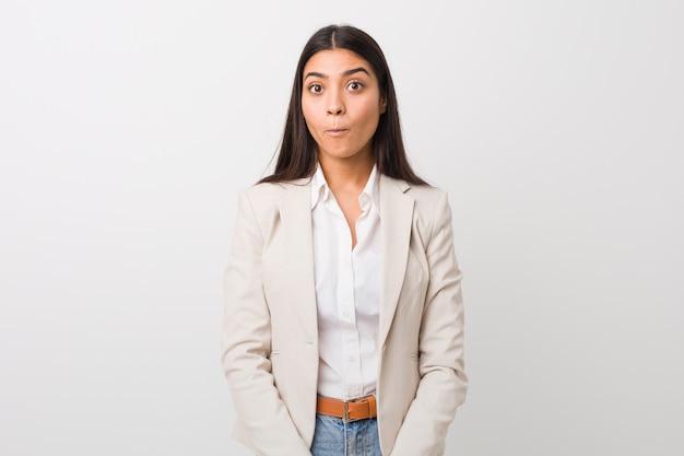 白い壁に対して隔離される若いビジネスアラブ女性は肩をすくめ、目を開けて混乱しています。