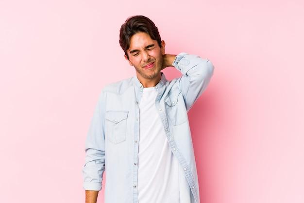 Молодой кавказский человек представляя в розовой стене изолировал страдая боль в шее из-за сидячего образа жизни.
