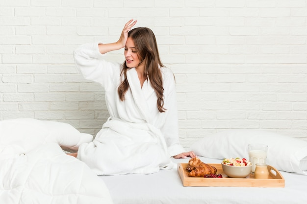 Молодая кавказская женщина на кровати забывая что-то, шлепая лоб с ладонью и закрывая глаза.
