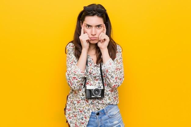 Молодая брюнетка путешественник женщина сосредоточена на задаче, сохраняя указательные пальцы, указывая головой.