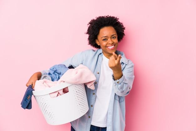 Среднего возраста афро-американских женщина, делая прачечная изолированные указывая пальцем на вас, как будто приглашая подойти ближе