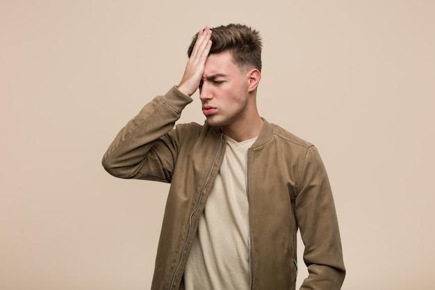 Молодой кавказский человек нося коричневую куртку забывая что-то, шлепая лоб с ладонью и закрывая глаза.