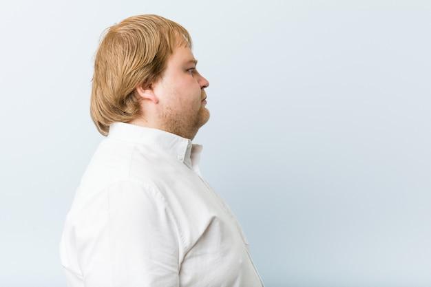左を見つめる若い本物の赤毛のデブ男、横向きのポーズ。