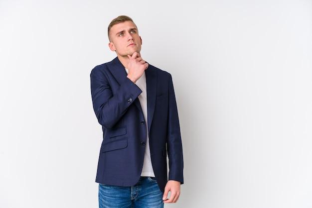 疑わしいと懐疑的な表情で横に探している若いビジネス白人男。