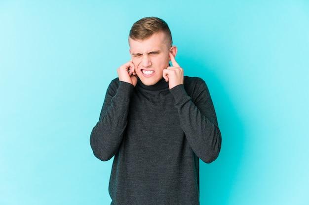 Молодой кавказский человек на голубых ушах заволакивания стены с руками.