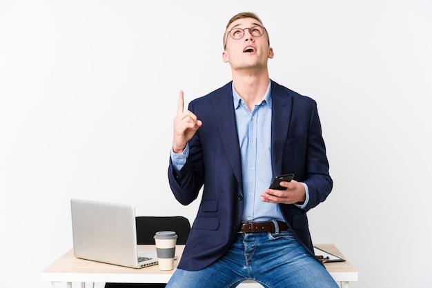 Молодой деловой человек с ноутбуком, указывая вверх ногами с раскрытой пасти.