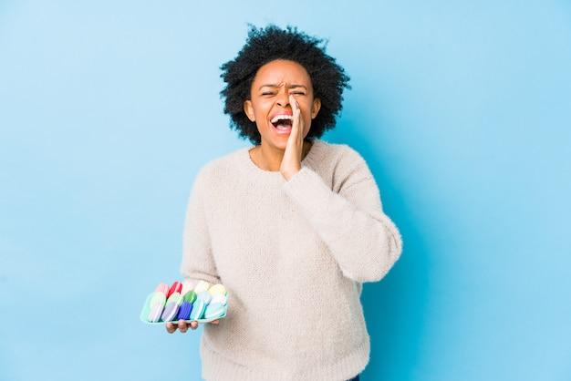 中年のアフリカ系アメリカ人女性は、正面に興奮して叫んで分離マカロンを食べる。