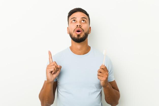 開いた口で逆さまに指している歯ブラシを保持している若い南アジアの男。
