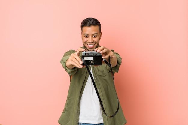 Молодой южно-азиатский путешественник фотографировать с ретро камеры.