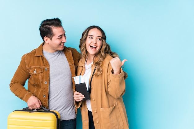 旅行の準備ができている若いカップルは、親指の指を離れて、笑いと屈託のないポイントを分離しました。