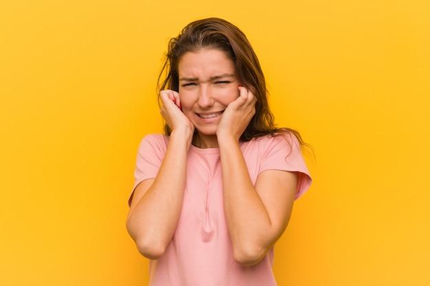 彼女の手で彼女の耳を覆う黄色の壁に分離された若いヨーロッパの女性。