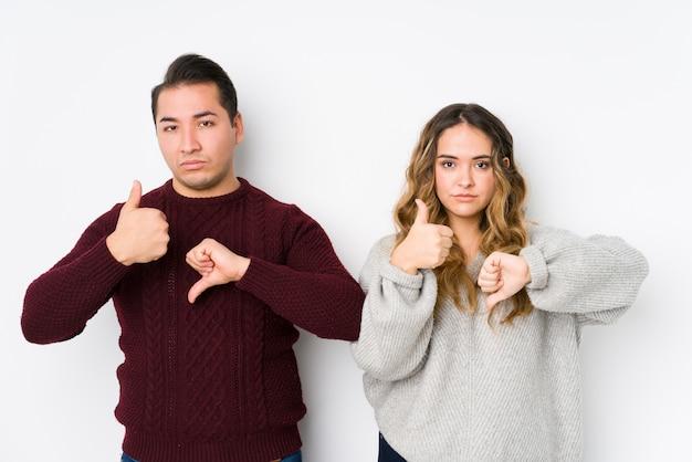 親指と親指を示す白い壁でポーズをとって若いカップル、難しいコンセプトを選択