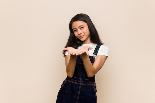 手のひらで何かを保持しているピンクの壁にコートを着て、若いかわいい中国のティーンエイジャー若いブロンドの女性