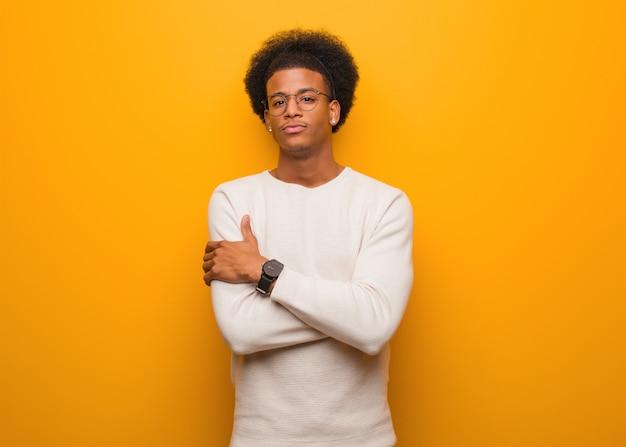リラックスした腕を渡るオレンジ色の壁の上の若いアフリカ系アメリカ人の男