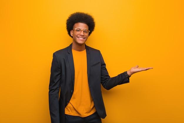 手で何かを保持しているオレンジ色の壁の上の若いビジネスアフリカ系アメリカ人