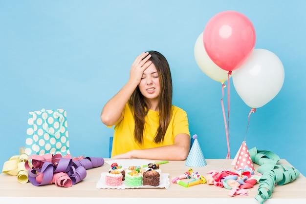 Молодая кавказская женщина организуя день рождения забывая что-то, шлепая лоб с ладонью и закрывая глаза.