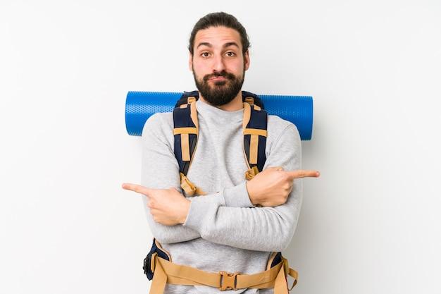 Молодой рюкзаком человек, изолированные на белой стене указывает в сторону, пытается выбрать один из двух вариантов.