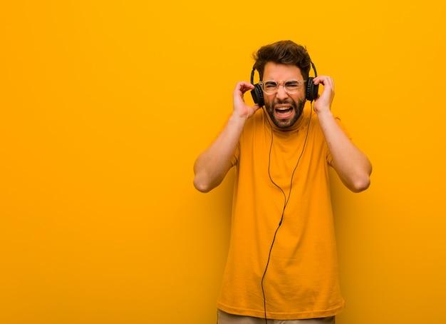 Молодой человек слушает музыку, закрывая уши руками