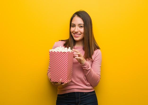 Молодая милая женщина держит ведро попкорна веселый с большой улыбкой