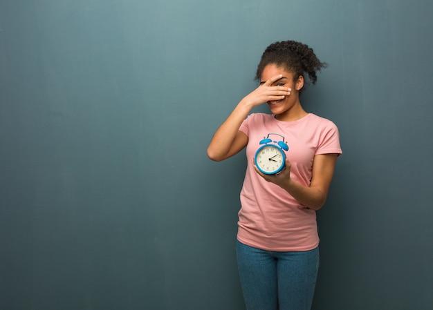 若い黒人女性は恥ずかしいと同時に笑っています。彼女は目覚まし時計を持っています。