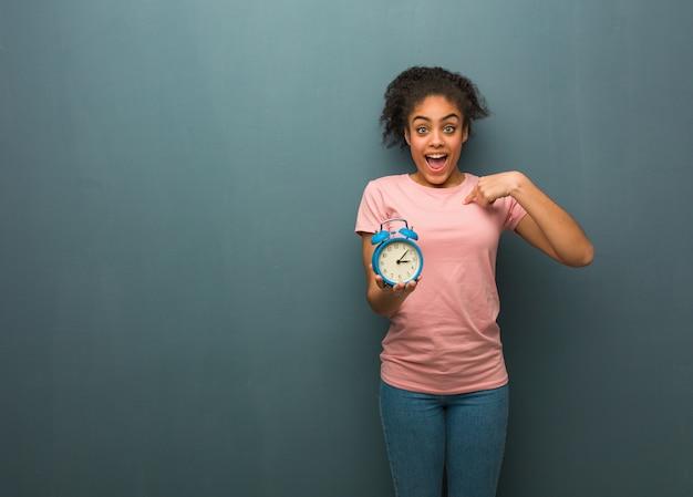 若い黒人女性は驚き、成功と繁栄を感じています。彼女は目覚まし時計を持っています。