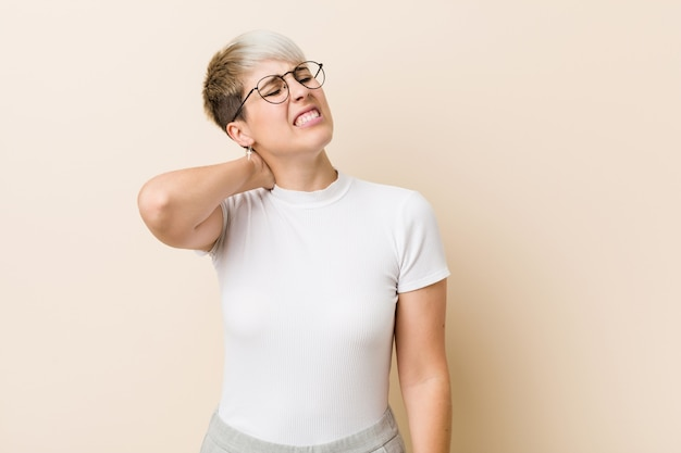 Молодая подлинная естественная женщина нося белую рубашку страдая боль в шее из-за сидячего образа жизни.