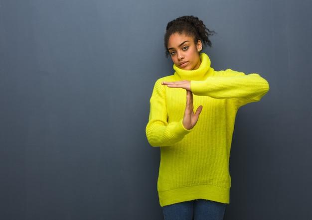 タイムアウトジェスチャーを行う若い黒人女性