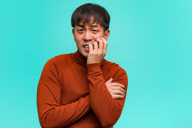 爪をかむ若い中国人男性、神経質で非常に不安