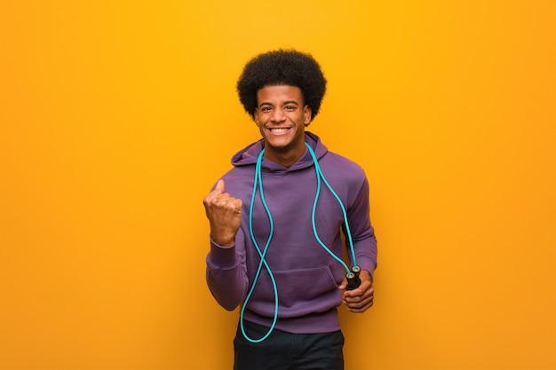縄跳びを持って若いアフリカ系アメリカ人のスポーツの男は驚きとショック